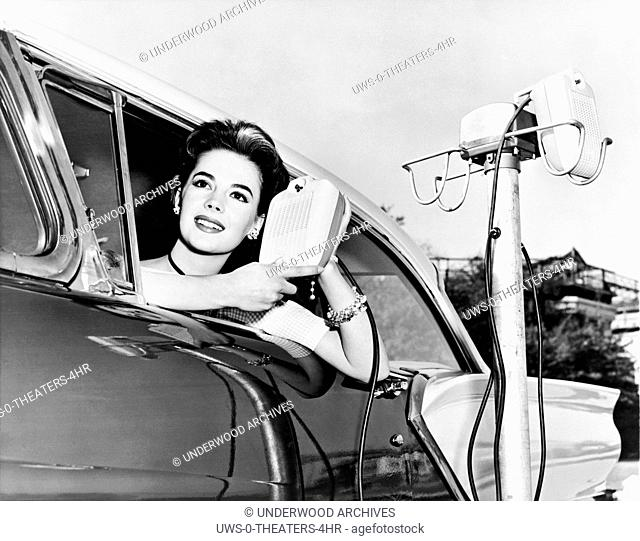 Hollywood, California: 1957.Natalie Wood displays the new drive in-movie speakers as she leans out of her car window