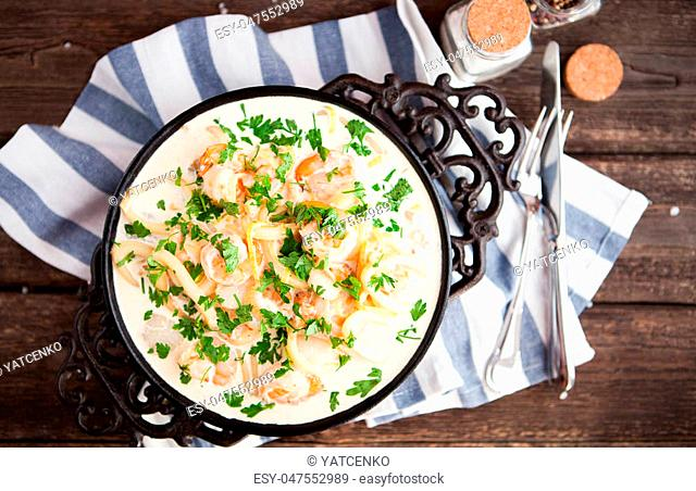 seafood - shrimp and squid with white cream sauce on frying pan, rustik style