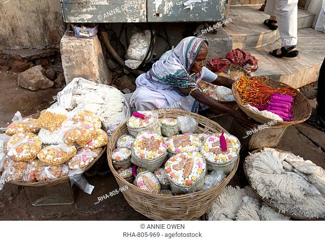 Woman in white sari, selling puja offerings from baskets in the street near the Hindu Jagannath temple dedicated to Lord Vishnu, Puri, Odisha, India, Asia