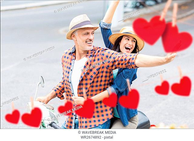 Excited couple waving hands while riding scooter
