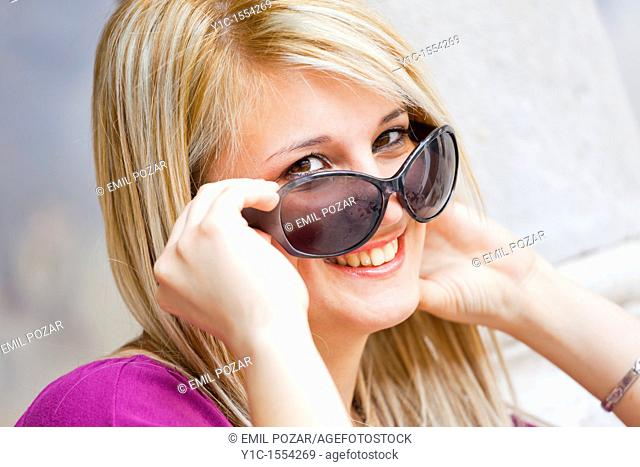 Attractive young woman happy and smiling looking over sunglasses