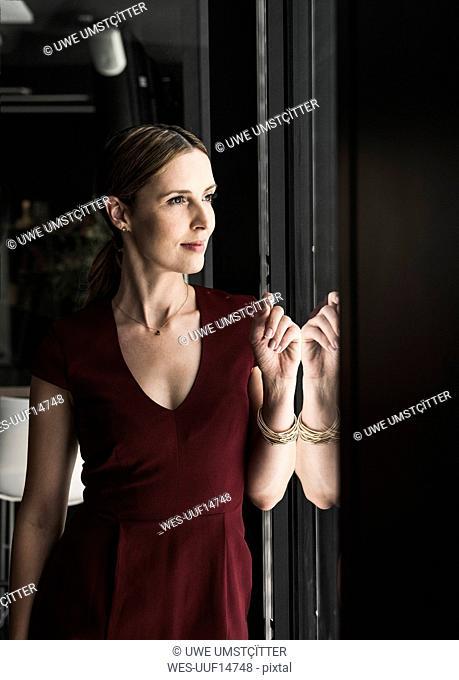 Woman wearing burgundy dress looking out of window