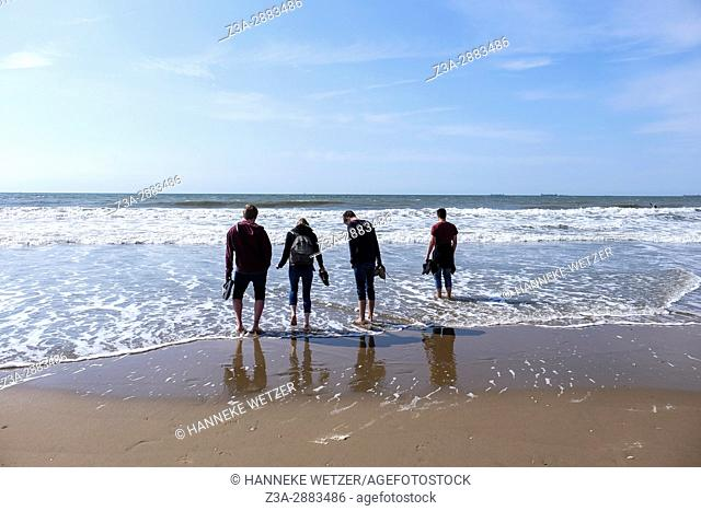 Four friends seen from the back at the beach of Scheveningen, The Hague, The Netherlands, Europe