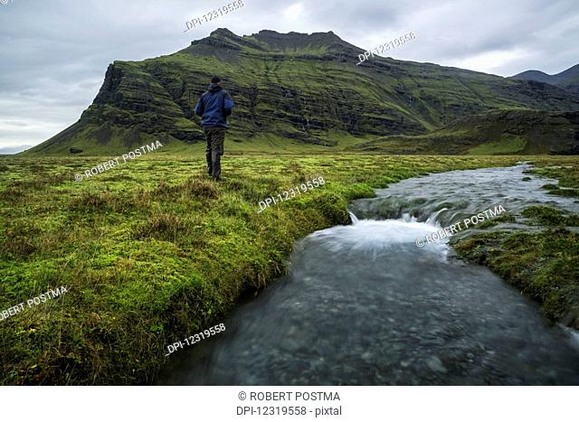 Man standing in the Icelandic wilderness beside a stream along the south coast of Iceland; Iceland