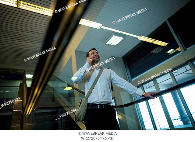 Handsome man talking on mobile phone on escalator