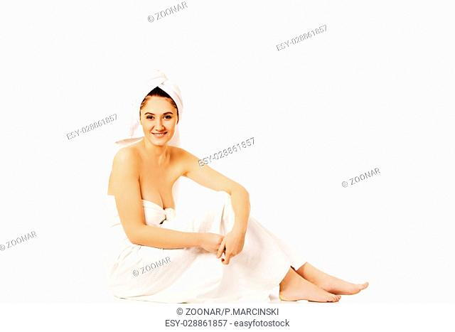 Young smile woman wrapped towels sitting
