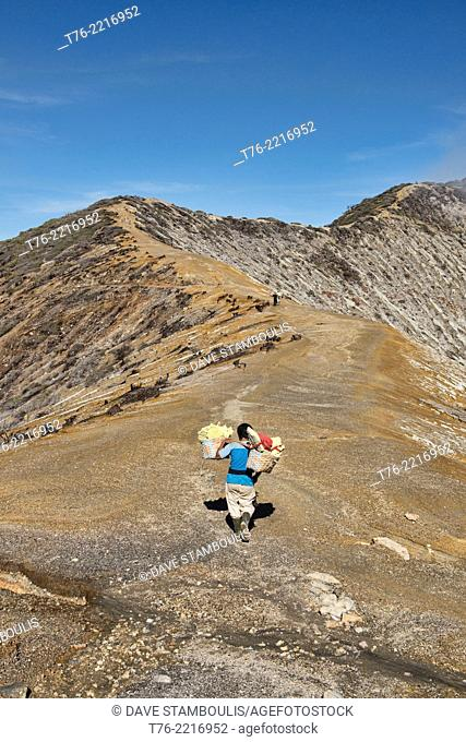 Miner carrying a heavy load of sulphur at the Kawah Ijen volcanic crater, Java, Indonesia
