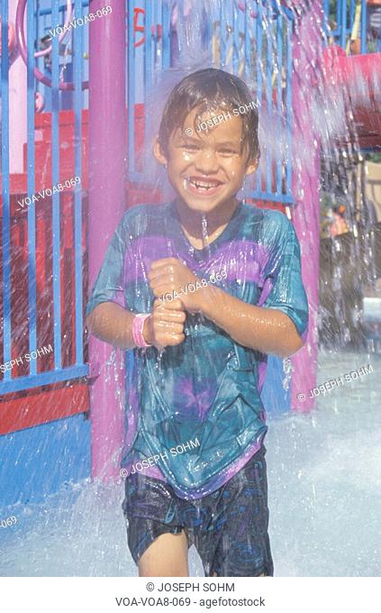 A boy under a water fountain at Raging Waters amusement park, Los Angeles, CA