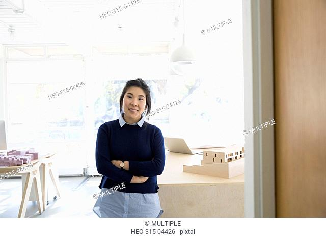 Portrait confident female architect with arms crossed in office