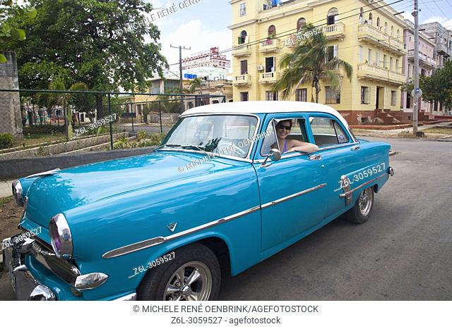 Tourist woman driving a Classic Ford car in Havana Cuba
