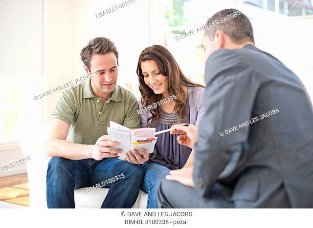 Hispanic couple talking with financial advisor
