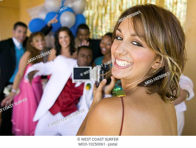Well-dressed teenager girl video taping friends at school dance