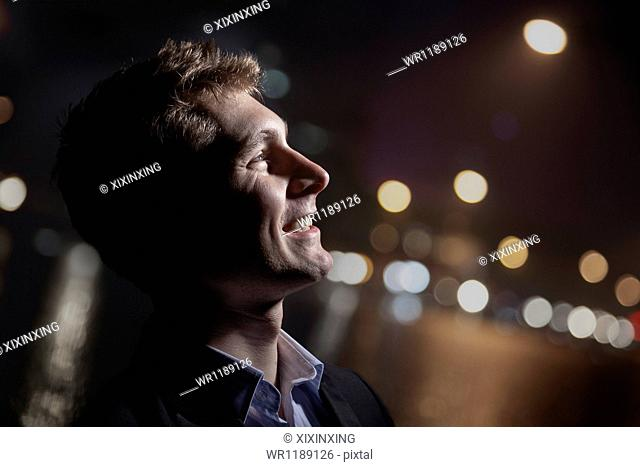 Portrait of smiling young man, profile, bright light shining on face, studio shot