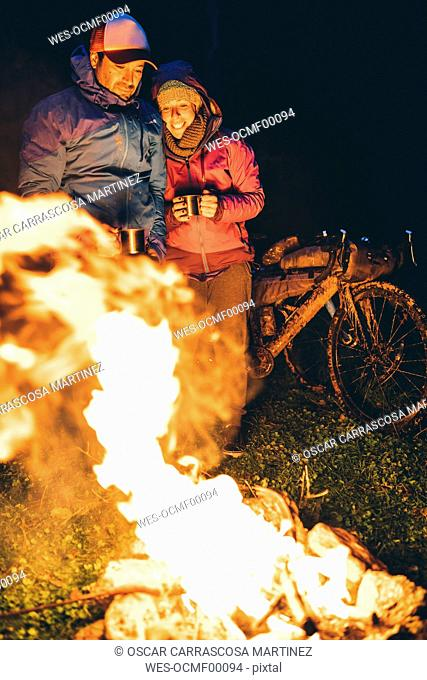 Couple with with bikes standing at camp fire looking at flame by night