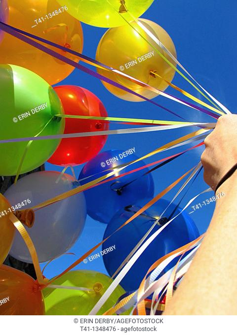 A woman's hand holding a bunch of birthday balloons