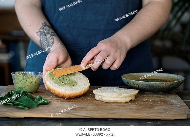 Woman preparing vegan burger, spreading avocado cream on bread roll