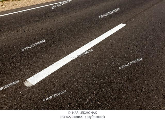 photographed close-up of road marking is located on the roadway, white line on the pavement