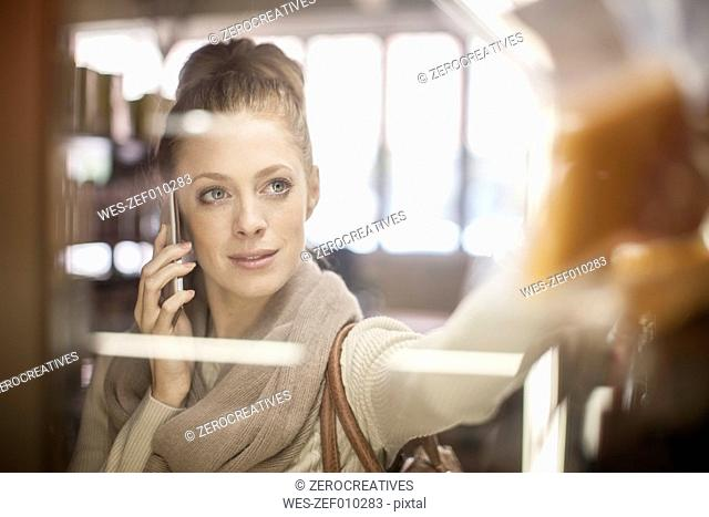 Woman on cell phone taking product in shop