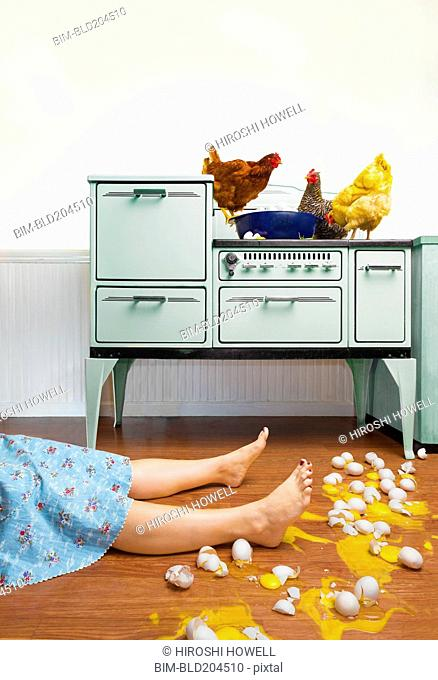 Caucasian woman on kitchen floor with broken eggs
