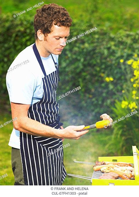Man inspecting lamb chop at barbecue