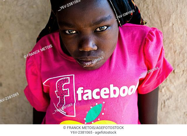 Village girl with a hunchback ( Oromiya state, Ethiopia). Facebook is written on her t-shirt