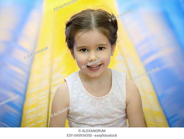 Joyful little girl playing on a inflatable bounce trampoline outdoors on sunny summer day. childhood concept