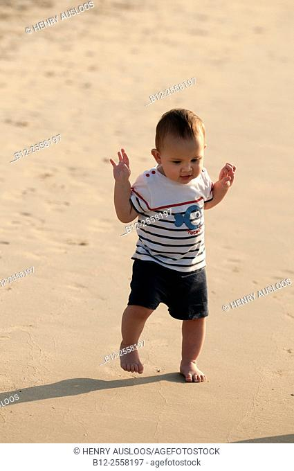 Toddler on the beach, first steps on the sand