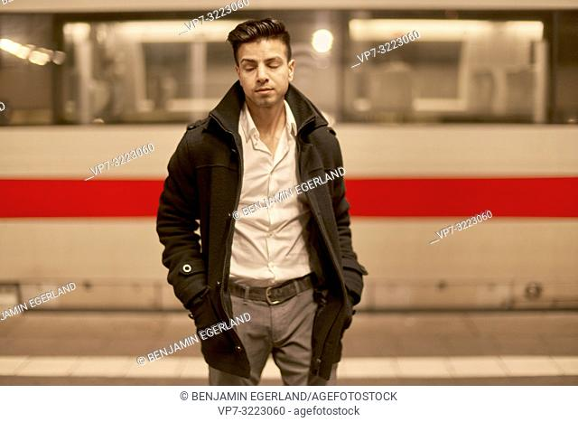 young tired man in front of train at train station with closed eyes, Afghan ethnicity, in Munich, Germany