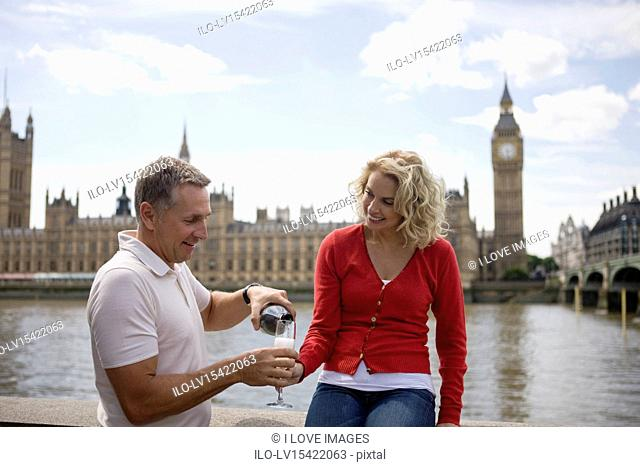 A middle-aged couple in front of the Houses of Parliament, man pouring champagne