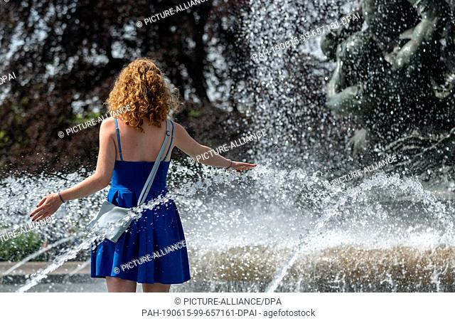 15 June 2019, Saxony, Dresden: Nina from Dresden walks through a fountain at Albertplatz to cool down. Photo: Robert Michael/dpa-Zentralbild/dpa