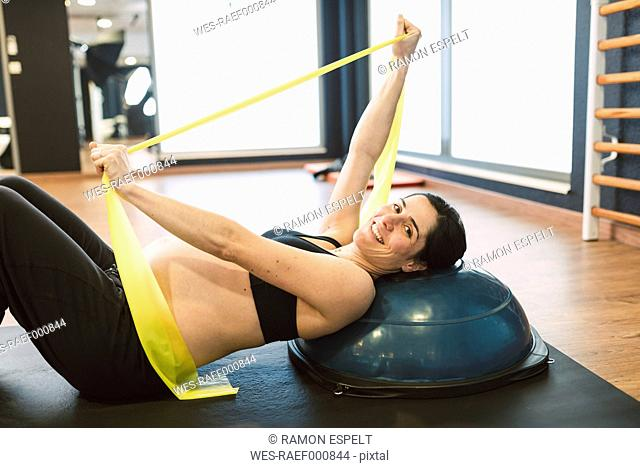 Pregnant woman doing pilates exercises with an elastic band