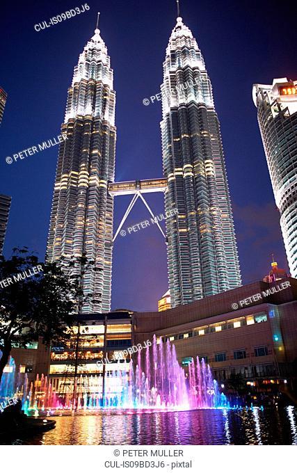 Petronas towers illuminated at night, low angle view, Kuala Lumpur, Malaysia