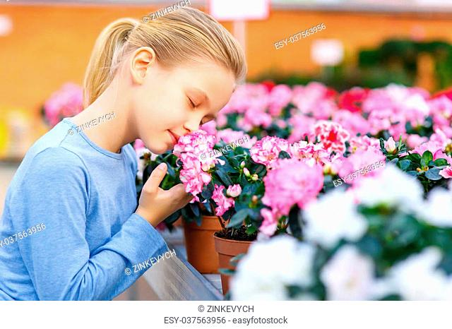 Sniff up the scent. Little girl squatting down and inhaling a pleasant flower smell