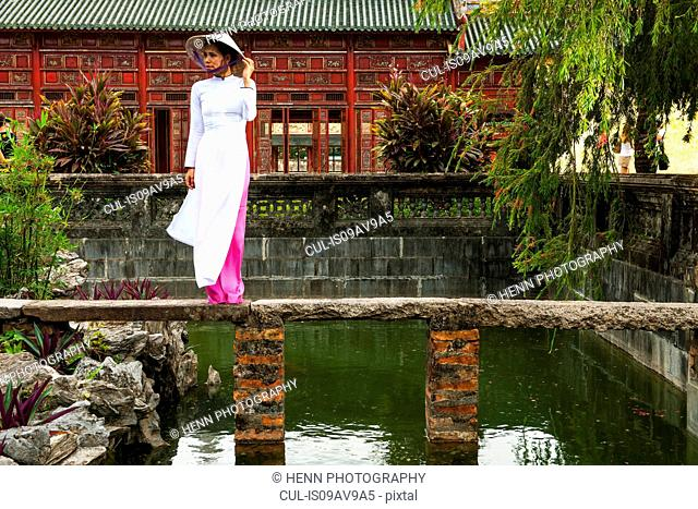 Full length front view of mid adult woman wearing ao dai dress and conical hat standing on foot bridge looking away, Hue, Vietnam