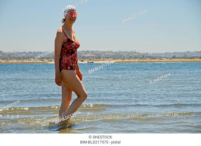 Caucasian woman walking in waves on beach