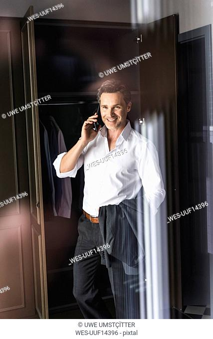 Smiling businessman on cell phone at wardrobe at home