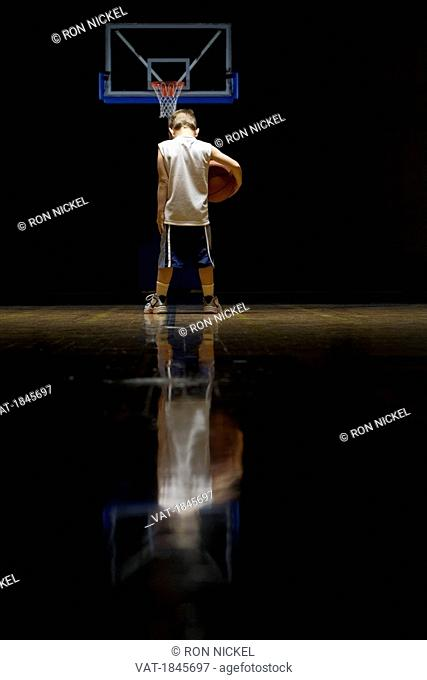 Young boy standing on basketball court looking solemn