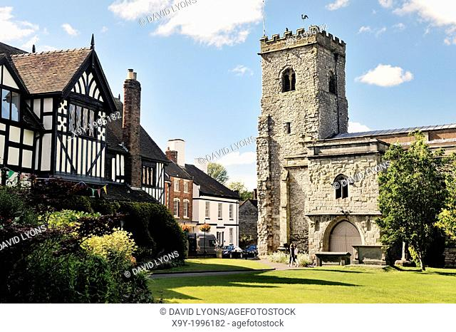 Holy Trinity Parish Church in the village of Much Wenlock, Shropshire, England. 16 C half-timbered Guildhall on left