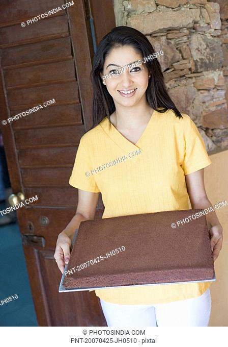 Portrait of a young woman holding a tray of cake