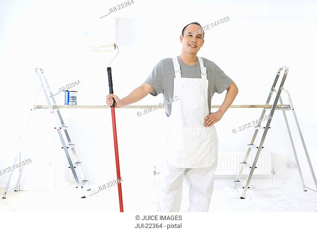 Smiling man holding paint roller with ladders and wood plank in background