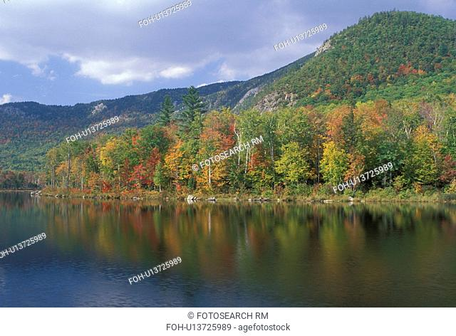 NH, Basin Pond, New Hampshire, White Mountain National Forest, Colorful fall foliage reflects in the calm waters of Basin Pond in the White Mountain Nat'l...