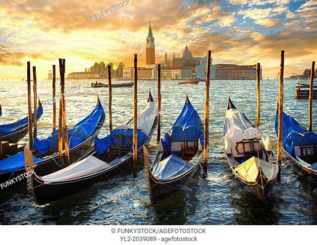 Sunset view of gondolas at St Mark's Square with the island of San Giorgio Maggiore behind , with its church front designed by Andrea Palladio and begun in 1566