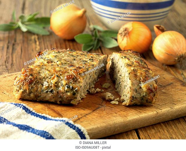 Roasted pork with sage and onion stuffing on rustic chopping board
