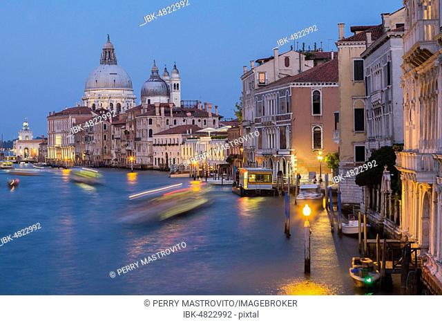 Grand Canal with light trails from water taxis, vaporettos in movement plus Renaissance architectural style palace buildings and Santa Maria della Salute...