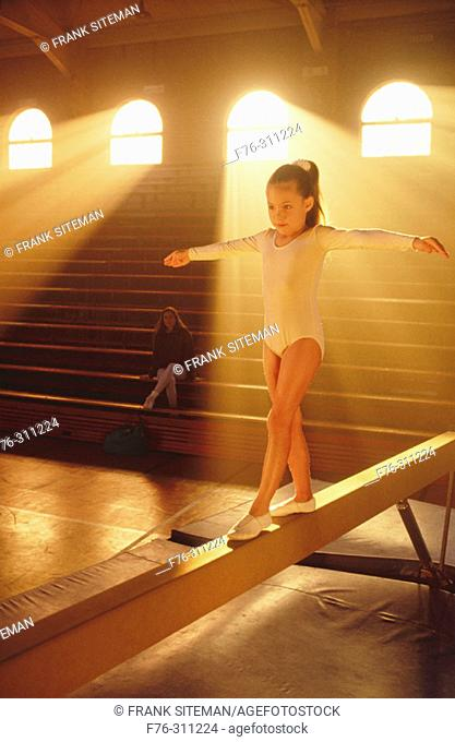 Young girl practicing on balance beam