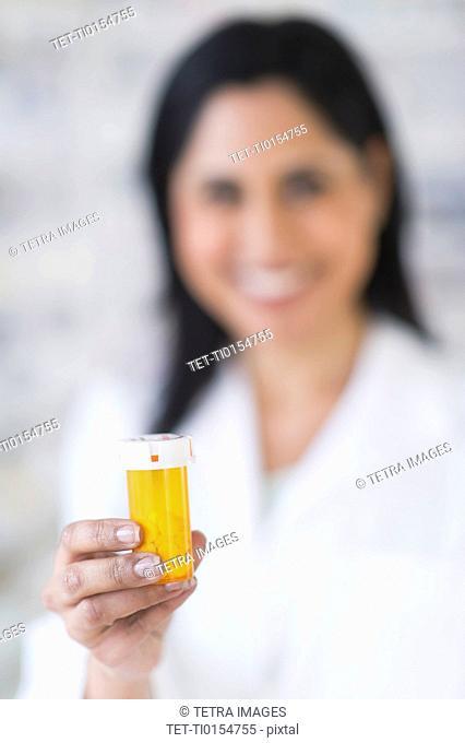 Hand of pharmacist holding pill bottle