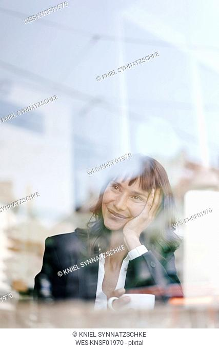 Businesswoman sitting in cafe with laptop, smiling and thinking