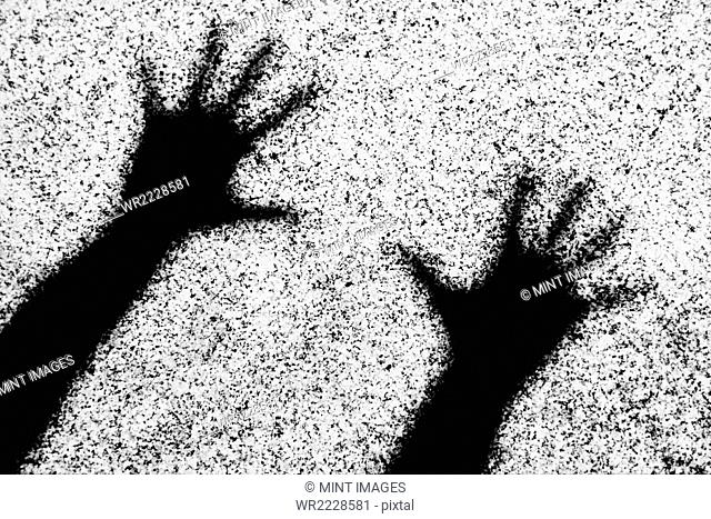 Shadow of two human hands with outstretched fingers on a wall