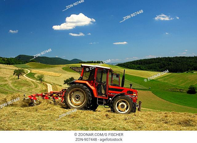 Traktor beim Heumachen auf Wiesen im Schweizer Mittelland, Kanton Aargau, Schweiz / Tractor making hay on meadows in the Swiss Central Plateau, canton of Aargau