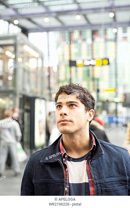 Man looking away at railroad station